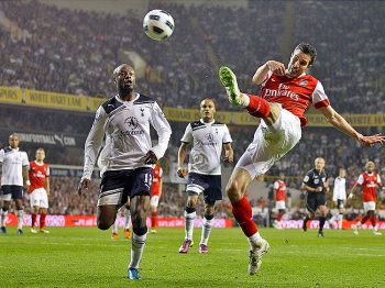 Arsenal's Robin Van Persie goes airborne while taking a shot against Tottenham Hotspur in Wednesday's North London derby. (Adrian Dennis/AFP/Getty Images)
