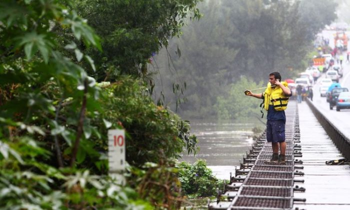 An emergency worker measures the height of the Hawkesbury River in Richmond, Australia, on March 3. (Marianna Massey/Getty Images)