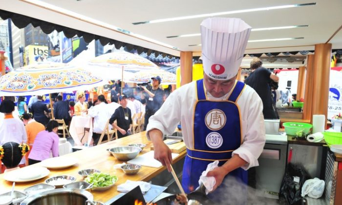 A chef cooks an authentic Chinese dish in Times Square during the 2011 International Chinese Culinary Competition. This September, celebrity chefs will join Chinese chefs in firing up their woks in Times Square. (Dai Bing/The Epoch Times)