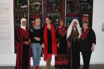 NEW WORK: Participants of the project Women Embroider Their Dreams pose in front of their work with Orna Goren (second from the left), founder of the museum and treasurer of the project, in the middle. (Courtesy of Zeev Dekel)