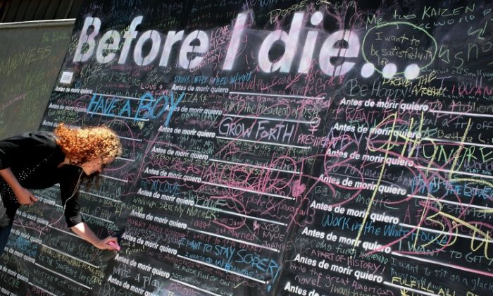 Local resident Kate Schaefer writes on a Before I Die public art display that invites people to share what is the most important thing they want to do before dying, May 11 in Washington, D.C. Before I Die was an idea originating with New Orleans artist Candy Chang who had transformed the side of an abandoned house in her neighborhood into a giant chalkboard for people to reflect what is important and meaningful to them. Local D.C. resident Sophie Miller set up the wall and with her friend Travis Moore funded it in memory of their grandparents. (Alex Wong/Getty Images)