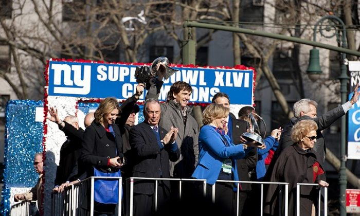Giants quarterback Eli Manning hoists the Lombardi Trophy over his head while Mayor Michael Bloomberg watches the crowd in the Super Bowl parade on Tuesday. (Dai Bing/The Epoch Times)