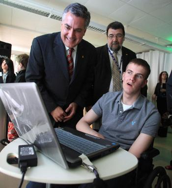 Children's Hospital of Eastern Ontario (CHEO) teen patient Jacob Doyle explores Upopolis, the first online social network at CHEO in Ottawa, while TELUS Business Solutions president Joe Natale (left) and CHEO president Michel Bilodeau look on, in May 2009. Upopolis is a child-friendly communication and education portal designed to keep kids informed and in touch during their hospital stay. (Patrick Doyle)