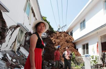 WORST MAY STILL COME: A Chinese woman looks at buildings damaged by a flood-triggered landslide in southwest Sichuan Province's Hanyuan County on July 27. The landslide left 21 people missing as torrential rains forced officials to shut boat traffic throu (STR/AFP/Getty Images)