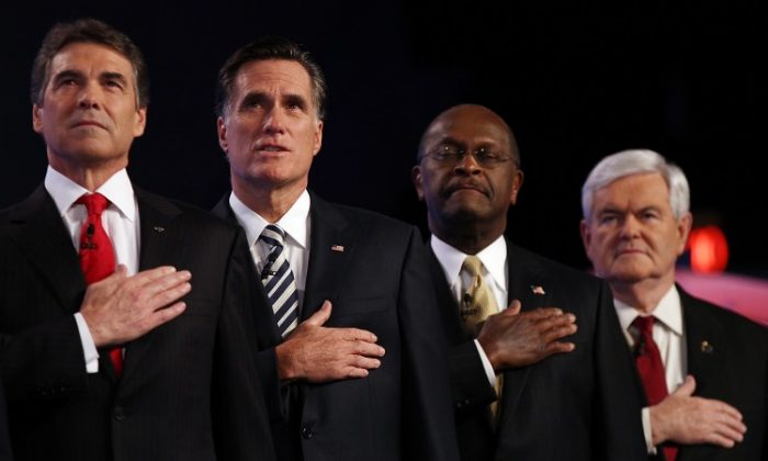 Republican presidential candidates (L-R) Texas Gov. Rick Perry, former Massachusetts Gov. Mitt Romney, former CEO of Godfather's Pizza Herman Cain and former Speaker of the House Newt Gingrich place their hands over their hearts during the national anthem prior to a debate at Constitution Hall in D.C. Nov. 22. Since Cain announced suspension of his campaign on Saturday, others in the field will await his choice for endorsement. (Win McNamee/Getty Images)