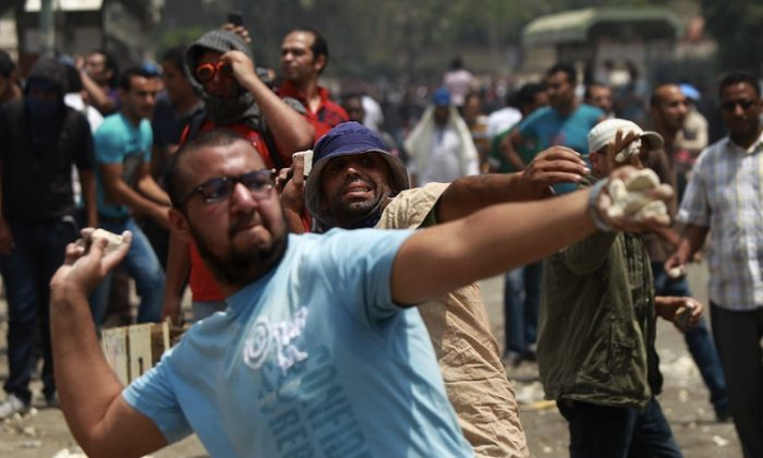 Egyptian anti-military protesters throw stones during clashes with unidentified attackers in the Abbassiya district of Cairo on May 2. (Khaled Desouki/AFP/GettyImages)