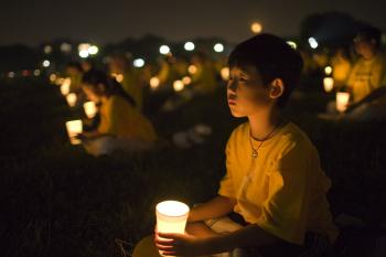 LITTLE BOY: A candlelight vigil at the Washington Monument on July 18 to commemorate Falun Gong practitioners who have been persecuted in the past nine-years. (John Yu/The Epoch Times)