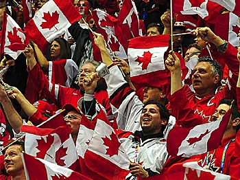 Canadian fans wave flags before the Men's preliminary Ice Hockey match Canada against USA at the XXI Winter Olympic games in Vancouver. At no other time or place would one see such overt patriotism from Canadians. (Luis Acosta/AFP/Getty Images)