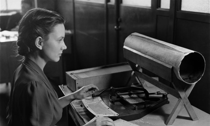 A woman operates a card puncher as part of an old tabulation system used by the U.S. Census Bureau to compile the thousands of facts. The National Archives will offer a digital release of data collected from the 1940 census on April 2. (U.S. National Archives/Public Domain)