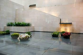 The Water Garden in the lobby, a very Asian and serene feature. Granite weirs and a reflecting pool with planters sit beyond the lobby's glass wall. (Charlotte Cuthbertson/The Epoch Times)