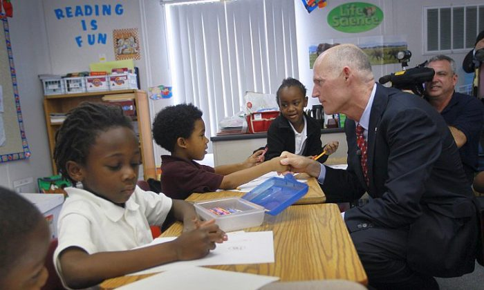 Florida Gov. Rick Scott greets students during a 2011 visit to the Florida International Academy charter school in Opa Locka, Fla. Charter schools are gaining traction as part of education reform initiatives in Southern states. (Joe Raedle/Getty Images)