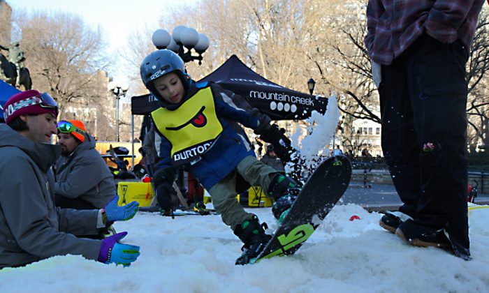 "Gabriel Crandall, 6 , perfects his ""rocky to fakie"" trick while snowboarding for the first time at Thursday at Union Square Park. (Benjamin Chasteen/The Epoch Times)"