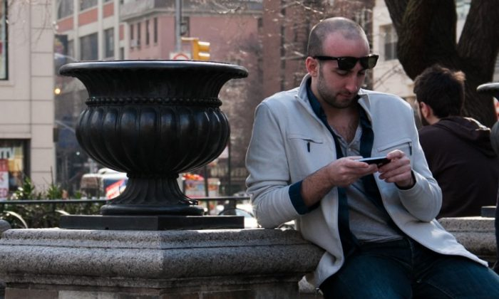 A man uses his smartphone in Union Square Park in Manhattan on March 8. (Benjamin Chasteen/The Epoch Times)