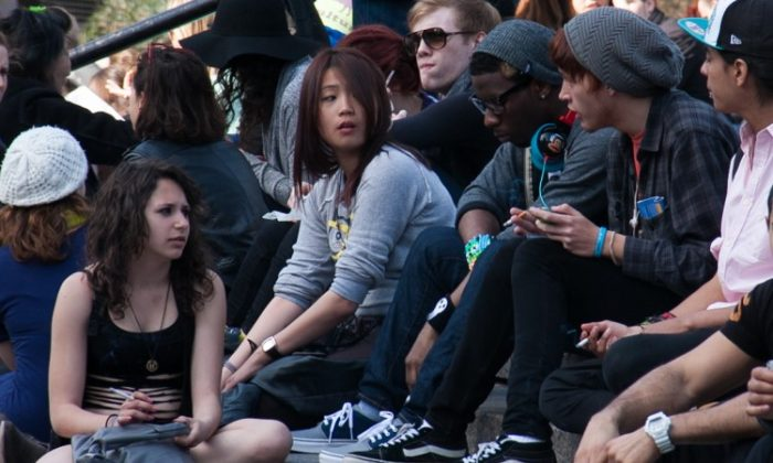 Teens smoking cigarettes on the steps in Union Square park in Manhattan on March 8. According to a report by the U.S. Surgeon General, one in three Americans between the ages of 18 and 26 now smoke. (Benjamin Chasteen/The Epoch Times)