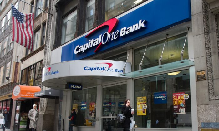 Pedestrians pass by a Capital One bank branch in Midtown Manhattan on March 16. Capital One Financial Corp. said Thursday it is selling $1.25 billion in new stock, which will help fund its growth from a regional bank to a banking giant with national presence. (Benjamin Chasteen/The Epoch Times)