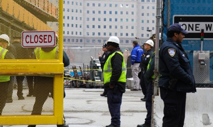 Construction workers and police officers stand in front of a truck that was crushed by metal beams as they fell from a crane when its cable snapped at 4 World Trade Center on Thursday. (Benjamin Chasteen/The Epoch Times)