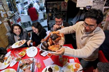 Tourists share barbecued meat at 'Los Canallas' restaurant in downtown Santiago. (Geraldo Caso/AFP/Getty Images)