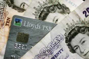 CASH OR CREDIT? A chip-and-PIN card is mixed in with Bank of England notes. (Christopher Furlong/Getty Images)