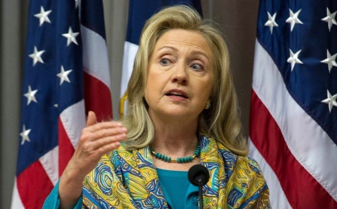 Dressed in aqua for World Water Day, U.S. Secretary of State Hillary Rodham Clinton remarks on a recent intelligence report linking several national security threats to water problems. (Karen Bleier/AFP/Getty Images)