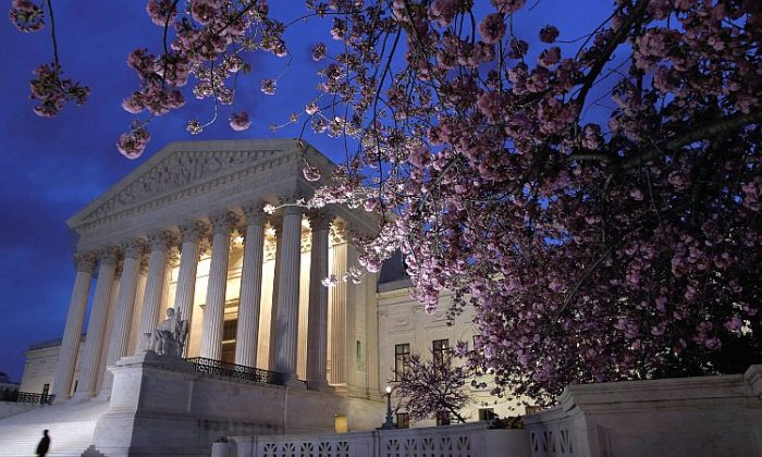 A security officer walks along the west front of the U.S. Supreme Court Building on March 28, after the court heard the fourth and final oral arguments of the Patient Protection and Affordable Care Act, dealing with Medicaid expansion. (Chip Somodevilla/Getty Images)