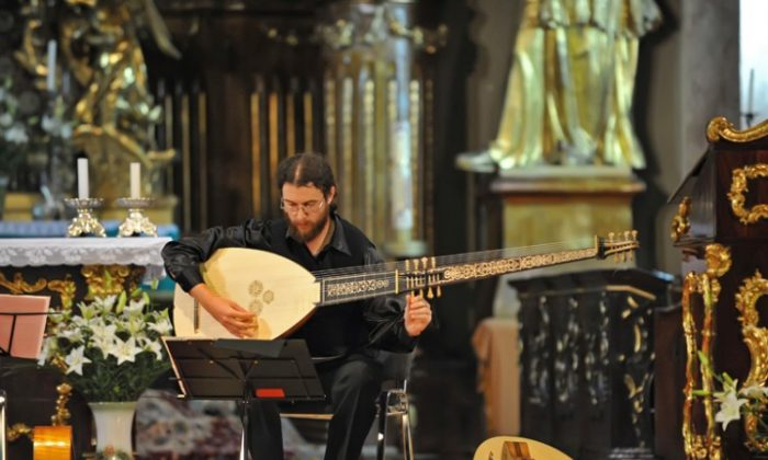 "Hera singing with the theorbo during a concert in Timisoara. (Courtesy of Caius Hera)""][/caption]Romanian lute player Caius Hera's love affair with the lute began in his room in Timisoara, Romania where he imitated the sound of the lute on his guitar. His passion led him to Basel, Switzerland and there, under the tutelage of the famous lute master Hopkinson Smith, young Hera reached the level of lute mastery that he'd always dreamed of.  Currently, Hera is working on projects with Hungarian singer Judit Andrejszki, with most of their concerts performed in Eastern Europe. In May, Hera will perform Renaissance music with Judit Andrejszki and the famous Hungarian folk singer Márta Sebestyén in Budapest. At the end of August, he is preparing a big tour in Romania, Hungary, and other nearby countries.  His First Lute  Hera had already studied classical guitar and music theory on his own in high school and only became acquainted with the lute in 2000 at the West University of Timisoara. It was then that he started experimenting with his guitar, trying to make it sound like a lute.  ""I simply liked it and tried to see how it would sound on my guitar. It sounded good, but I felt that it wasn't exactly what I wanted. Lute strings are thinner, and there are some things about the instrument's construction [that differs]. The tensions are different. The overall sonority of the instrument is far lower than that of the guitar. The guitar sounds loud and aggressive; the lute sounds soft, very soft,"" he said.  After searching for years, Hera found, in a small Romanian town, a violin maker able to make a lute for him—his first lute.  The violin maker wasn't what Hera was prepared for. ""'What do you want, kid? You want to ruin yourself?' was the answer to his order for a lute, Hera recalled. 'You better go do some pop music. You want to go down the road of no return? It's like a disease, kid. When you get one lute, you'll want another, and another.'""  But Hera replied, ""Give me a break, sir. Don't depress me. I want a lute! I've dreamed of having my own lute for years. Now I finally found you, so please make one for me.""  ""The man said, 'Okay, kid. I'll make a lute for you.'""  On New Year's Eve, 2004, Hera had his first lute in hand. But when he started to pluck the lute strings the next day, he was totally disappointed. The sound had no color.  He called the violin maker, ""'Sir, what have you given me here? This doesn't sound right!' and the man replied, 'Kid, you don't know what you've gotten yourself into. It doesn't work that way—switching from a guitar to a lute, and that's it? You need a specific technique. You have to study the technique of interpretation, as if you were going from the piano to the harpsichord. You must realize this is another tool. You must take master classes.'""  Unwilling to renounce his dream of mastering the lute, Hera went to Lake Balaton in Hungary. There was a music festival that year and the great lute master, Hopkinson Smith, was invited. Hera met him and arranged some master classes with him and then he said to himself, ""This is good! I'm finally on the right track."" But he wanted more. He wanted to sit there and study everything from the beginning. Hera remembers: ""Hopkinson said, 'No problem, you can find me in Basel.'""  With extraordinary guts, Hera took all of his savings, booked a train ticket and—bang!—he went to Basel. He studied with Hopkinson Smith for two years. And, although he wondered about it, because it was enormously expensive, he ended up studying with the greatest and the most famous musicians of early music—with Crawford Young, studying Medieval to early Renaissance lute playing, and with British lutenist Anthony Rooley.  Hera went to Basel with one lute, but he returned with many other old instruments. In addition to the Renaissance lute, he mastered the vihuela da mano, a baroque lute with 13 strings; a theorbo, or long-necked lute; an oud, a pear-shaped string instrument; a Baroque guitar; a Renaissance lute and many other instruments with six, seven, and ten strings.  ""It was just as the violin maker said, 'That thing will get you, kid. You won't be able to stop. You'll always want new instruments and you're always going to call me and tell me that you need a tool shank with this or that, or another with—I don't know what—and in the end you will end up with four or five instruments that are the same, with only small differences between them.'""  [video w=""590"