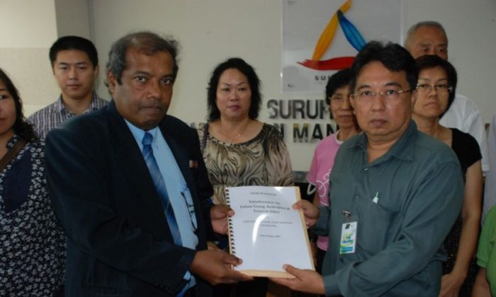 Muhammad Sha'ani (L), commissioner of SUHAKAM, accepted a memorandum on May 9 from Raymond Ng (R), spokesperson for Falun Gong practitioners in Malaysia.