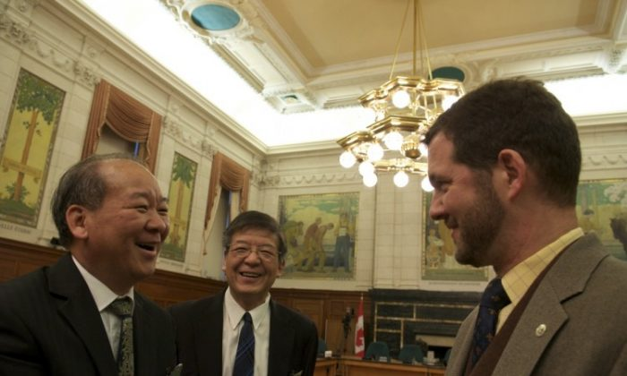 Brothers Mingli Lin and Shenli Lin laugh with Tory MP Scott Reid before recounting dark tales of incarceration in China. (Matthew Little/The Epoch Times)