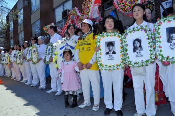 Falun Gong practitioners hold wreaths of practitioners who have been tortured to death in China. (Mingguo/The Epoch Times)