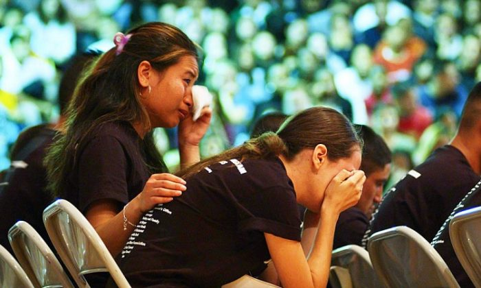 "Two high school students cry during the reading of emotional letters between ""dead"" students and their parents at the end of the Every 15 Minutes program at West Covina High School May 2002 in Los Angeles, Calif. Every 15 Minutes teaches teens how someone is killed in an alcohol-related car crash every 15 minutes. (David McNew/Getty Images)"