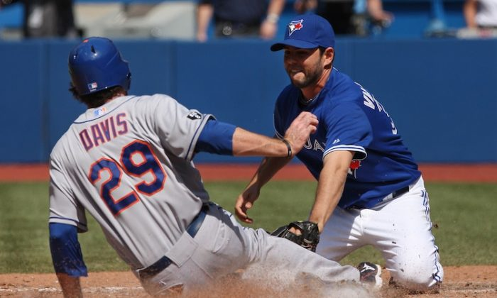 Ike Davis (L) was thrown out at the plate by catcher J.P. Arencibia after attempting to score following a wild pitch. (Tom Szczerbowski/Getty Images)