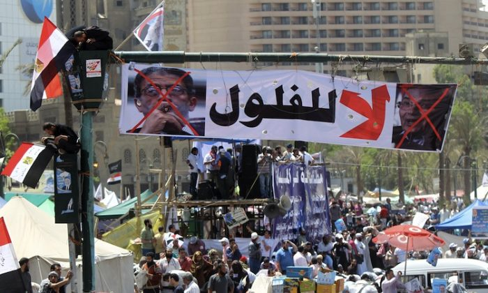 Egyptians sit on the traffic light decorated with a banner showing the portraits of former prime minister Ahmed Shafiq (R) and former Arab League general secretary Amr Mussa and which reads in Arabic 'no for the reminisce of the old regime', as thousands gather during a rally in Cairo's Tahrir Square on April 20. (Khaled Desouki/AFP/Getty Images)