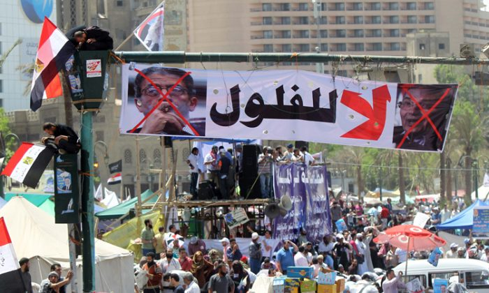 """Egyptians sit on the traffic light decorated with a banner showing the portraits of former Prime Minister Ahmed Shafiq (R) and former Arab League General Secretary Amr Moussa, which reads in Arabic """"No for the reminisce of the old regime,"""" as thousands gather during a rally in Cairo's Tahrir Square on April 20. (Khaled Desouki/AFP/Getty Images)"""