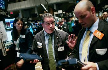 Traders talk on the floor near the end of the trading day at the New York Stock Exchange yesterday. Stocks closed down more than 700 points on Wednesday.  (Chris Hondros/Getty Images)