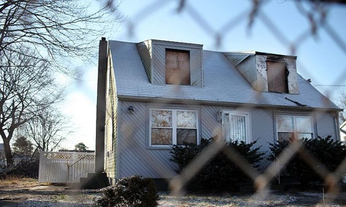 A foreclosed home stands boarded up on Feb. 9 in Islip, NY. A report released by RealtyTrac shows a slight increase in foreclosure-related filings for the month of January. (Spencer Platt/Getty Images)