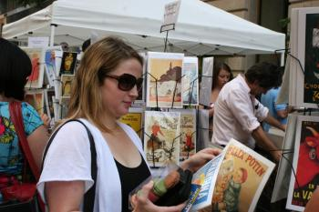 FRENCH ART: Onlookers browse through racks of famous French posters. (Diana Hubert/Epoch Times Staff)