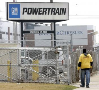 A man walks past the General Motors Powertrain Plant and toward the Chrysler Truck Plant in Warren, Michigan. GM announced last week that 7,500 United Auto Workers union members have accepted buyouts and early retirement packages. (Bill Pugliano/Getty Images)
