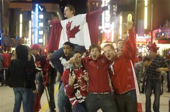 OLYMPIC REVELERS: Certified Canucks and other revelers frolic on Granville Street nightly in downtown Vancouver. Police say the partygoers have been relatively well-behaved.  (Matthew Little/The Epoch Times)