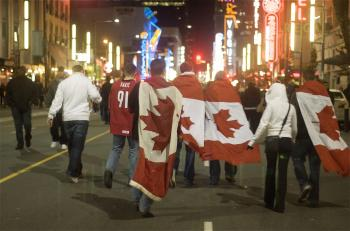Revelers wrap Canadian flags around themselves.  (Matthew Little/The Epoch Times)