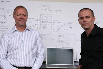 Green printer co-owners Brian Schindel and Alen Rokolj pose in front of a software programming map. The pair aim to revolutionize the printing industry with their software by making it easier for companies to implement green technologies. (Andrea Hayley)