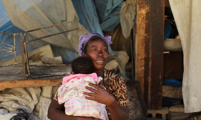 A woman holds her child in front of her temporary home on March 4, in Port-au-Prince, Haiti. While much of Haiti is still in crisis two years after the magnitude-7.0 quake, Western country aid budgets are shrinking amid the global recession. (Spencer Platt/Getty Images)