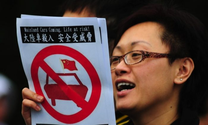 A woman holds a placard against allowing mainland Chinese drivers into Hong Kong at a demonstration in a park in Hong Kong on Feb 12. (Antony Dickson/AFP/Getty Images)