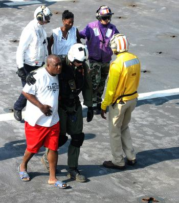 Navy flight deck personnel escort injured Haitians to the casualty receiving section of the USNS Comfort hospital ship on Jan. 20. (Jim Garamone)