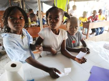 Three young girls attend a make-shift school set up by the Israeli organization PRODEV Foundation in Port-au-Prince on Feb. 8, 2010, as the population of Haiti strives to re-establish some degree of normalcy in their lives following the Jan. 12 earthquake. (Thony Belizaire/AFP/Getty Images)