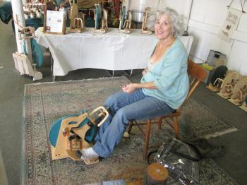 HITCHHIKER: Kathy Paul spins using a Hitchhiker, one of the smallest treadle wheels made. (Louise McCoy/The Epoch Times)