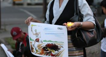 RIGHTS TRAMPLED: Tibet supporter holds a commentary cartoon on the Beijing Olympics during a candlelight vigil at the Chinese Consulate in Calgary on August 7.  (Neil Campbell/The Epoch Times)