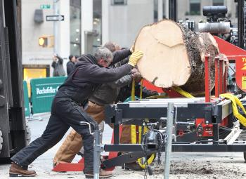 The Christmas tree that keeps on giving, the Rockefeller Center Christmas tree being milled down to lumber at Rockefeller Center on Saturday. (Gary Du/The Epoch Times)