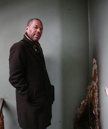STATE OF DISREPAIR: Nehemiah Bey of Northwest Bronx Community and Clergy Coalition stands in the hallway of a grossly neglected residential building in the Bronx.  (Tara MacIsaac/The Epoch Times)