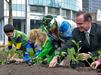 RENEWAL: Parks Commissioner Adrian Benepe (R) plants the first crops at Battery Park in hundreds of years. The park will be home to a temporary urban farm, tended by local schools, for the next two years.  (Tara MacIsaac/The Epoch Times)