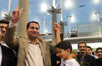 Iranian nuclear scientist Shahram Amiri holds his son's hand as he flashes the victory sign upon arrival at Imam Khomeini Airport in Tehran on July 15.  (Atta Kenare/Getty Images )
