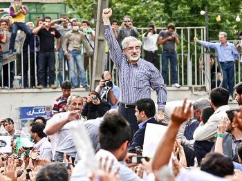 REFORM: Defeated reformist presidential candidate Mir Hossein Mousavi (C) raises his arms as he appears during a demonstration in the streets on June 15, 2009, in Tehran, Iran. (Getty Images)